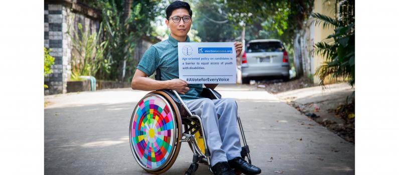 "A man using a wheelchair holds a sign that says, ""Age-oriented policy on candidates is a barrier to equal access of youth with disabilities."""
