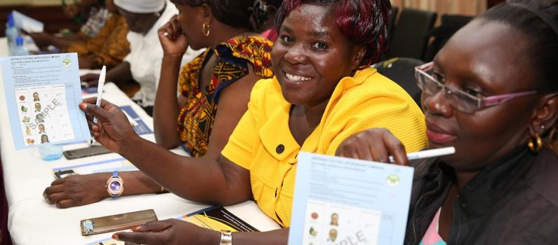 Chama women learn how to educate their communities on the correct way to mark a ballot paper with support from the IEBC while attending a training session.