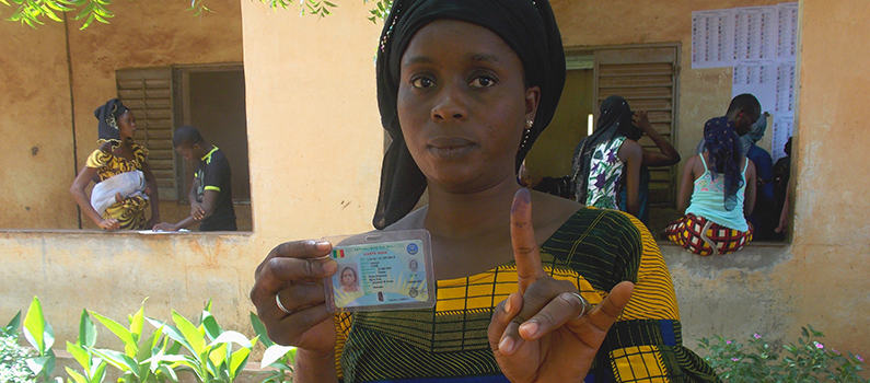 Voter holds up a voter ID and inked finger.